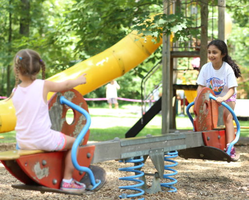 Female campers playing on teeter totter