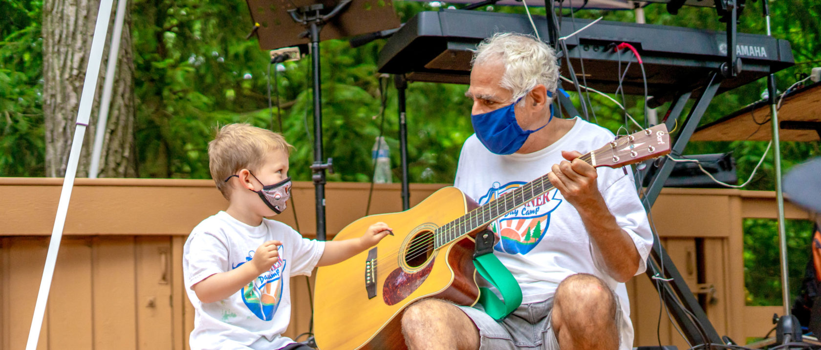 Male camper learns to play guitar from instructor with masks on