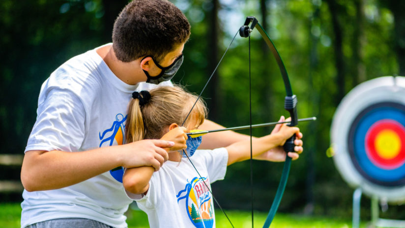 Male counselor leads camper at archery with masks on